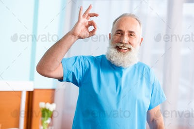 Senior bearded man in hospital robe smiling at camera and showing ok gesture