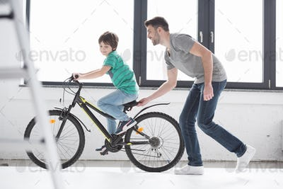 side view of young father helping son to ride bicycle