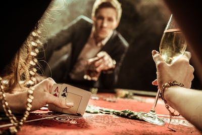 partial view of woman with drink looking at cards while playing poker