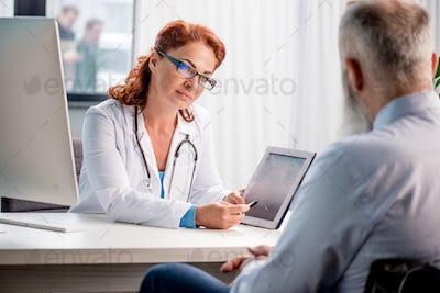 Smiling female doctor showing digital tablet to senior patient