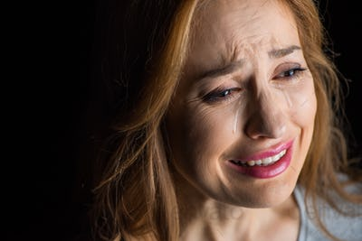 Close-up portrait of young beautiful woman crying  isolated on black