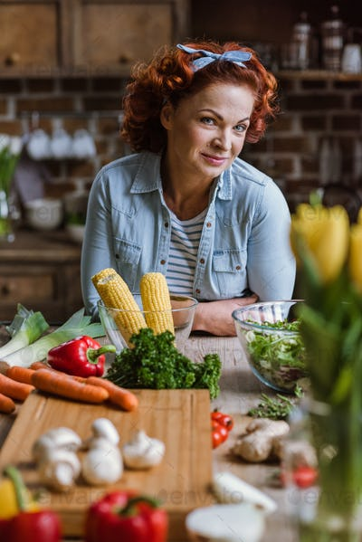 Mature woman standing at kitchen table full of fresh vegetables and looking at camera