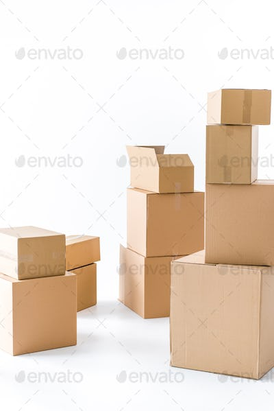 Piles of stacked brown cardboard boxes  isolated on white