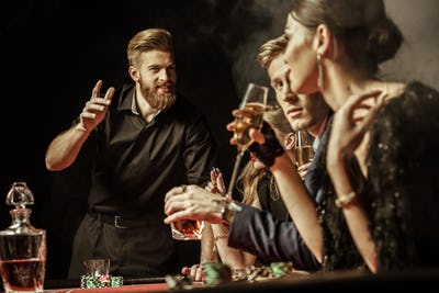 side view of men and women playing poker in casino