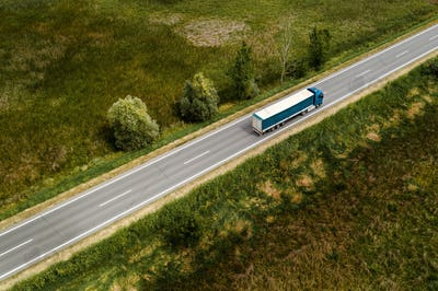 Large freight transporter semi-truck on the road, aerial view