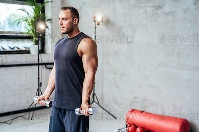 Serious bodybuilder with dumbells in hands in studio room