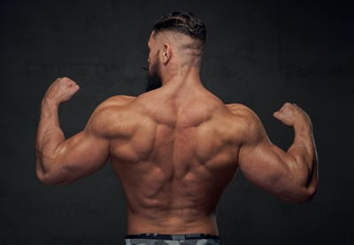 Muscular guy with huge biceps posing in gray background
