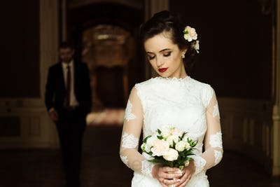 stylish luxury bride and handsome elegant groom on the background of rich interior in old building