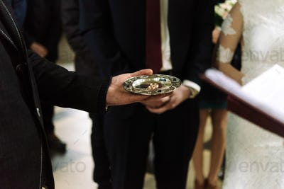 priest blessing luxury wedding rings in the old church