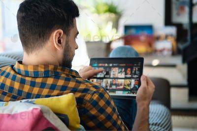 Man Choosing Movie For Streaming On Tablet