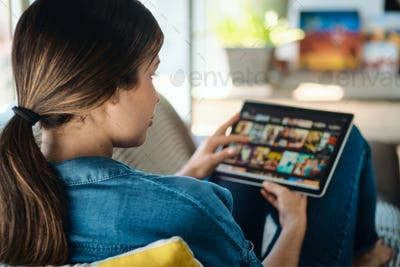 Woman Choosing Movie For Streaming On Tablet