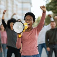 Black lady with megaphone leading group of demonstrators