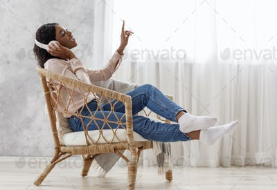 Joyful African Woman Singing While Listening Music With Wireless Headphones At Home