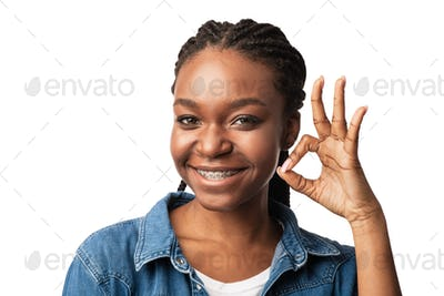 African American Woman With Braces Gesturing Okay Over White Background