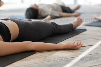 Unrecognizable woman lying on mat in corpse pose, practicing yoga in studio