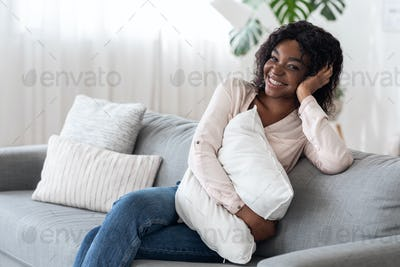 Domestic Portrait. Smiling African American Lady Posing On Cozy Sofa At Home