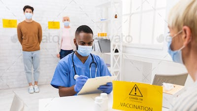 Doctor Working With Patients During Coronavirus Vaccination Campaign In Hospital