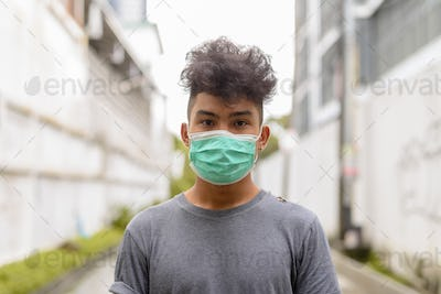 Young Asian man with curly hair wearing mask in the streets