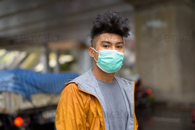 Young Asian man with curly hair wearing mask in the city streets outdoors