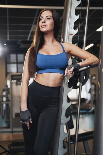 Glamour sportive brunette posing leaning barbell in gym