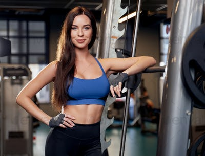 Sportswoman in blue shirt posing leaning on barbell in gym