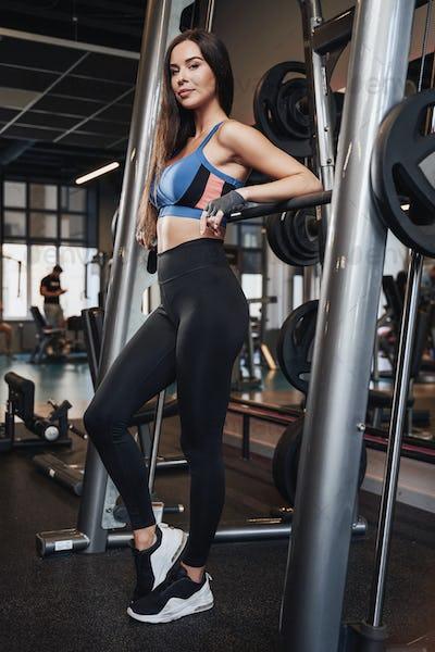 Sportive brunette with slim figure posing in popular sport club
