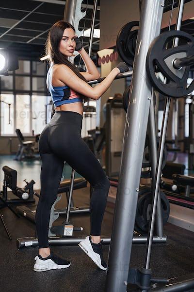 Slim brunette sportswoman posing near barbell in modern gym