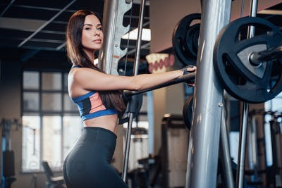 Dressed in sportswear pretty woman holding barbell in gym
