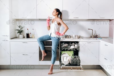 a housewife girl in pink gloves after cleaning the house sits tired in the kitchen.In the white