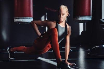 Blond sportswoman warming up in dark gym with shadows