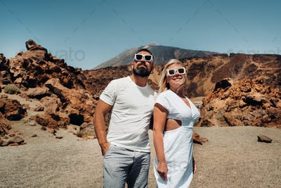 a guy and a girl in white clothes and glasses stand in the crater of the El Teide volcano, a Couple