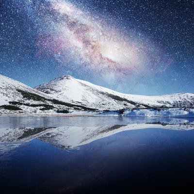 lake between snow-capped mountains. Fantastic starry sky