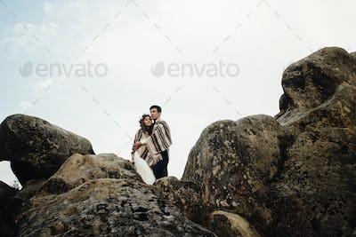 stylish gorgeous couple newlyweds hugging under rug