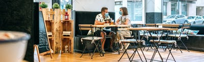 Couple with face mask having drinks in a cafe