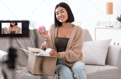 Happy asian woman recording product review for beauty blog