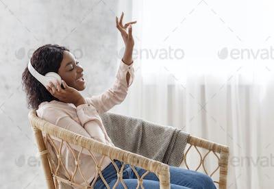 Favorite Leisure. Joyful Black Female In Wireless Headphones Listening Music And Singing