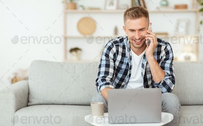 Portrait of smiling guy using pc talking on smartphone