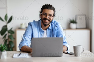 Happy Indian Freelancer Man Sitting At Desk With Laptop, Smiling At Camera
