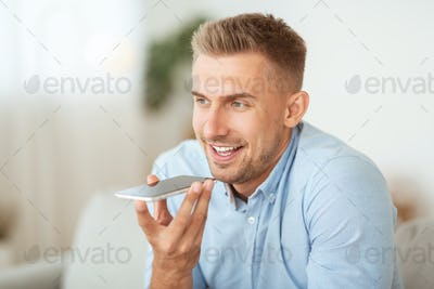 Young man using voice assistant on his smartphone