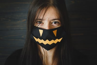 Coronavirus Halloween safe celebration, young female in evil face mask. Stay creative, stay safe