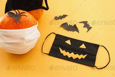 Halloween 2020 safe celebration. Evil face mask, pumpkin in mask, bat and spider decorations