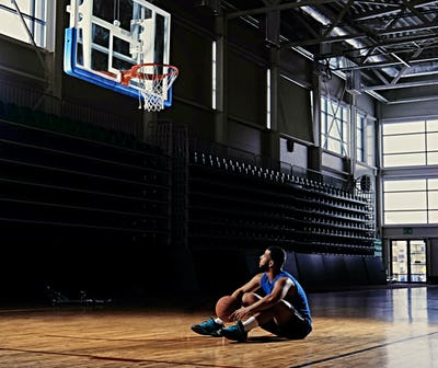 Basketball player sits on a field under the hoop.