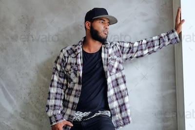 Black man posing near window with natural light.