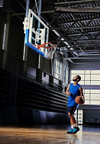Basketball player holds a ball over the hoop in a game hall.