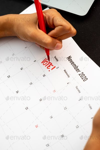 Woman writing on a calendar a vote reminder of the American president election day in 2020