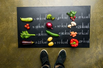 partial view of man standing near fresh vegetables and calories table, healthy lifestyle concept