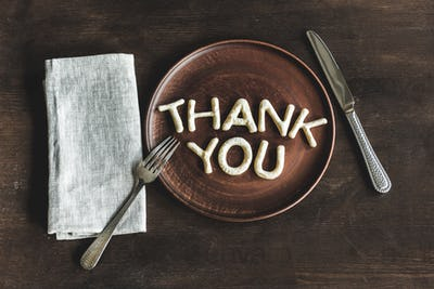 top view of thank you lettering made from cookie dough on wooden plate