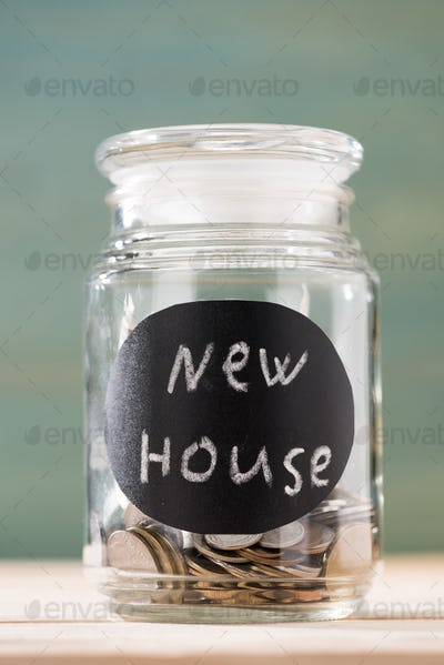 coins in glass can with sign new house on wooden table, piggy bank savings
