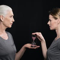 senior woman giving hourglass to his daughter isolated on black