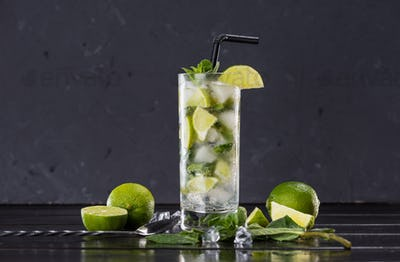 Close-up view of mojito cocktail in glass, sliced limes and mint on black, cocktail drinks concept